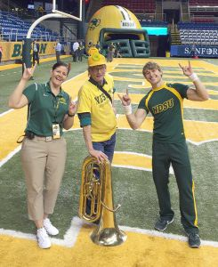Left, returning to NDSU for an alumni event was unique experience earlier this season, in October. Pelican Rapids Press managing editor Louis Hoglund, pictured at center, above joined the NDSU Gold Star alumni band to perform during the Homecoming football game.  He also had the opportunity to connect with Nick Thompson, right, a Pelican Rapids High School graduate who is a member of the cheer squad. At left, cheer team coach Verona Winkler.  Sidenote: It was also something of a family reunion for Hoglund––Coach Verona is his cousin.